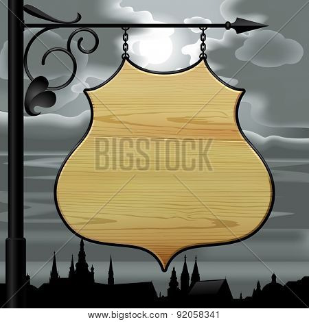 Vintage wooden street  signboard hanging on forged brackets against the background of the old city at night and cloudy sky with the moon. Contain the Clipping Path of signboard with brackets