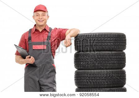 Young male mechanic in a gray jumpsuit leaning on a stack of tires and holding a clipboard isolated on white background