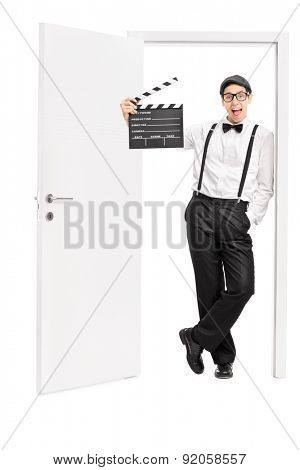 Full length portrait of a young movie director holding a clapperboard and leaning against the frame of an open door isolated on white background