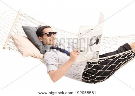 Relaxed young man reading a newspaper and lying in a hammock.The newspaper is custom made, pictures are my copyright. You can find them and the necessary Model Releases attached