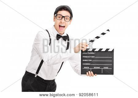 Young movie director holding a clapperboard and looking at the camera isolated on white background