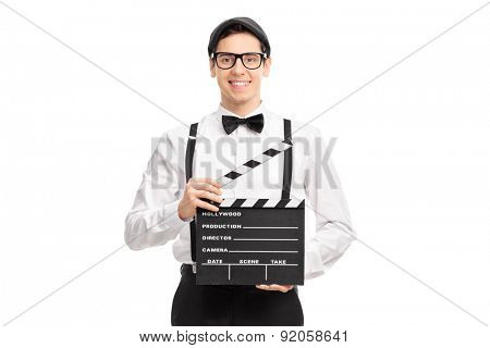 Young movie director holding a movie clapperboard, smiling and looking at the camera isolated on white background