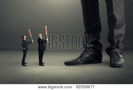 two small screaming businessmen holding placard and looking up at big legs over dark grey background