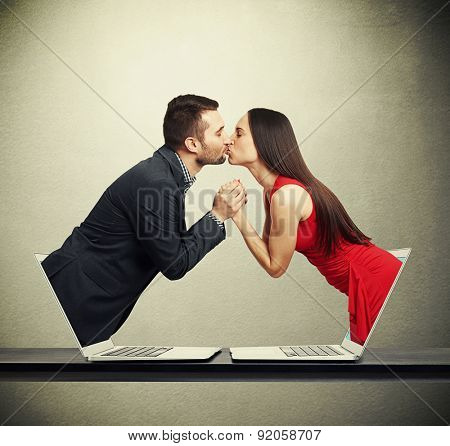 handsome man got out of the computer and kissing beautiful young woman who got out of another computer over dark background