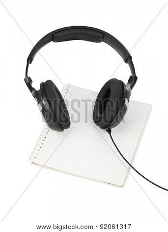 Headphones and notepad isolated on white background
