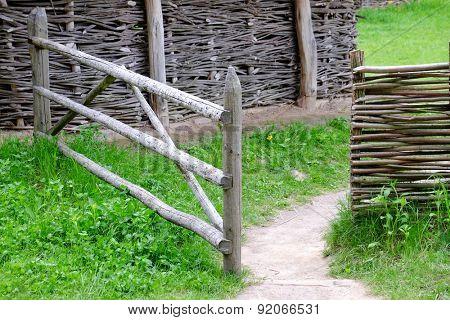 Wicker rustic fence in garden on grass background