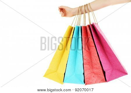 Female hand with colorful shopping paper bags isolated on white