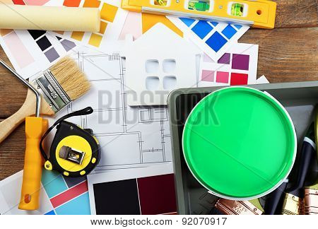 Construction instruments, plan, colorful paint samples and brushes on wooden table background