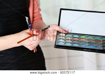 Female makeup artist with cosmetics at work close-up