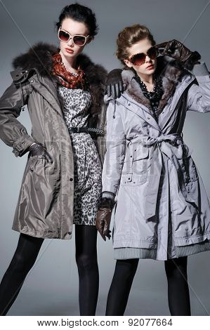 high young attractive two girl wearing fur coat on gray background