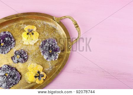 Candied sugared violet flowers on tray, on color wooden background