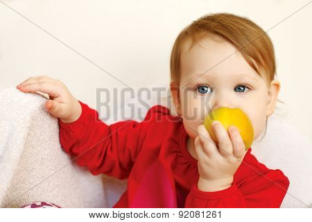 Beautiful baby girl eats red apple.