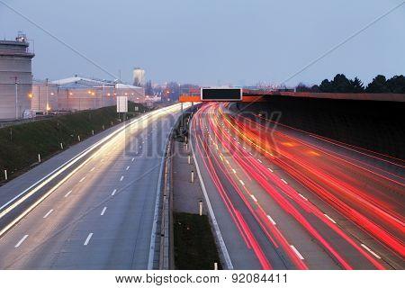 Speed Traffic At Dramatic Sundown Time - Light Trails On Motorway Highway At Night, Long Exposure Ab