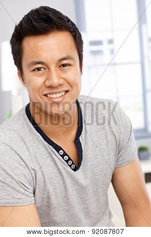 Closeup portrait of happy young Asian man smiling, looking at camera.
