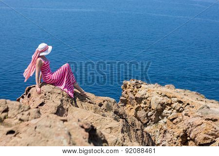 Woman In A Long Dress  Sitting On A Rock On The Sea