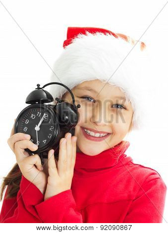 Girl In A Santa Hat Is Holding Alarm Clock