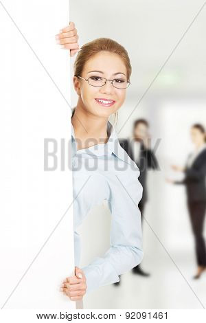 Beautiful young business woman presenting your product.