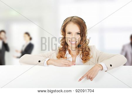 Smiling call center woman pointing empty banner.