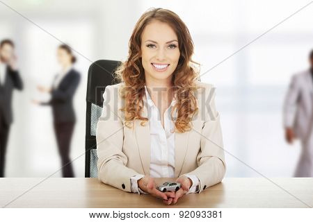 Business woman by a desk holding a toy car.