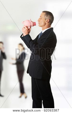 Mature businessman standing with piggybank.