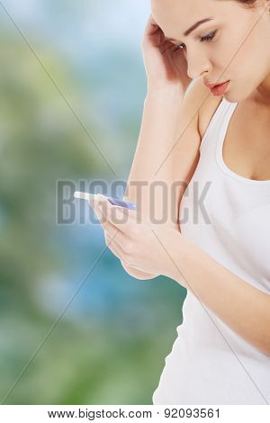 Young worried woman holding pregnancy test.