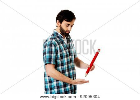 Young happy man writing with oversized red pencil.