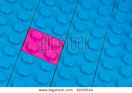 Pink building block in a field of blue ones