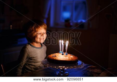 Little Kid Celebrating His Birthday And Blowing Candles On Homemade Baked Cake