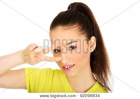 Young student woman showing victory sign on eyes.