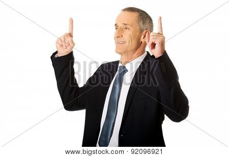 Smiling mature businessman pointing upwards.