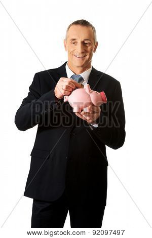 Mature businessman putting a coin to piggybank.