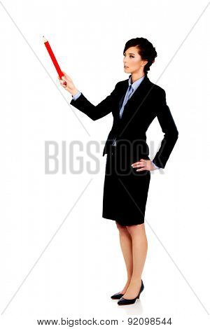Happy businesswoman pointing up with big pencil.