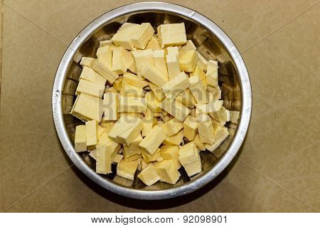 Sliced fresh cheese or paneer from South Asia kept on a vessel on a plain background