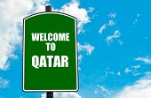 picture of qatar  - Green road sign with greeting message WELCOME TO QATAR isolated over clear blue sky background with available copy space - JPG