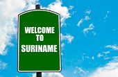 picture of suriname  - Green road sign with greeting message WELCOME TO SURINAME isolated over clear blue sky background with available copy space - JPG