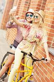 stock photo of tandem bicycle  - A picture of two girl friends riding a tandem bicycle and taking selfie in the city - JPG