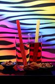 image of nibbling  - 2 drinks with straws and selection of nibbles against a multicolored background - JPG