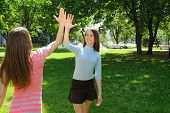 stock photo of goodbye  - Two girls say goodbye after exercise outdoors at park against the backdrop of greenery - JPG