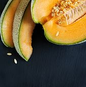 picture of cantaloupe  - Cantaloupe Melon Slices on black board with copy space - JPG