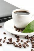 picture of coffee crop  - Cropped cup of black coffee with laptop saucer scattered coffee beans with leaf at breakfast on white background - JPG