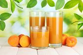 stock photo of apricot  - Glasses of apricot juice and fresh apricots on table on green background - JPG