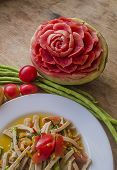 foto of green papaya salad  - Close up rose on watermelon carving and papaya salad with pork