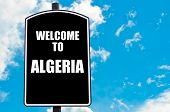 stock photo of algeria  - Black road sign with greeting message WELCOME TO ALGERIA isolated over clear blue sky background with available copy space - JPG