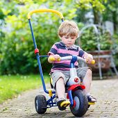 foto of four-wheel drive  - Active blond kid boy driving tricycle or bicycle in domestic garden - JPG