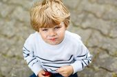 image of strawberry blonde  - Funny little kid boy eating fresh organic strawberries in domestic garden on warm summer sunny day - JPG