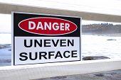 foto of slip hazard  - A danger sign warning about an uneven surface near an Australian beach - JPG