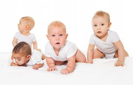 foto of babygro  - Curious looking group of babies crawl in a row wearing white bodysuit on the white background - JPG
