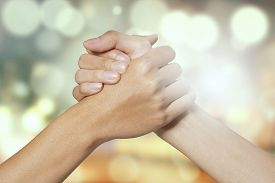 stock photo of joining  - Closeup of two hands joining together symbolizing to trust each other shot with a bokeh background - JPG
