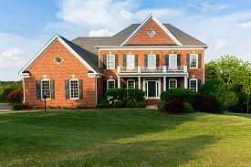 pic of in front  - Front of home and garage of large single family modern US house with landscaped gardens and lawn on a warm sunny summers day - JPG