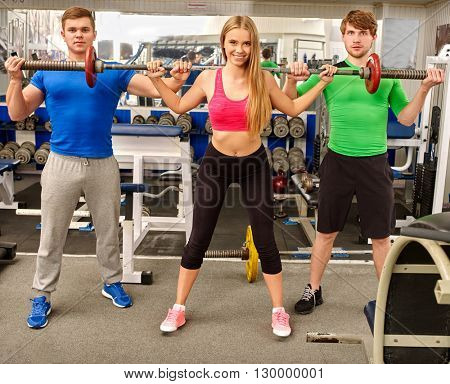 Group of people working with  barbell his body at gym. Two mens back up woman with barbell .